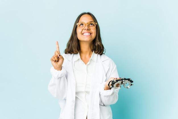 Молодая латинская женщина-окулист показывает обоими указательными пальцами вверх, показывая пустое пространство.