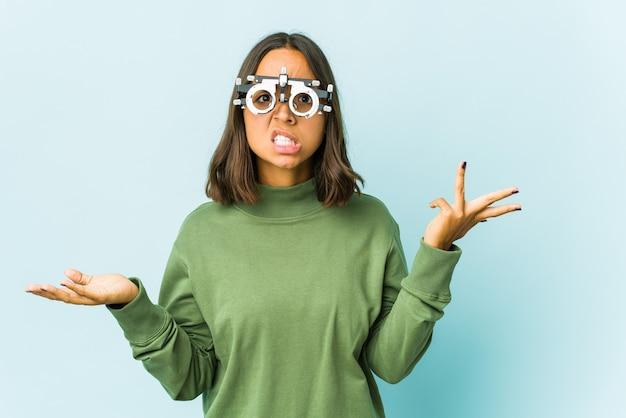 孤立した壁の上の若い眼科医ラテン女性は、コピースペースを保持するために混乱し、肩をすくめる疑わしい。