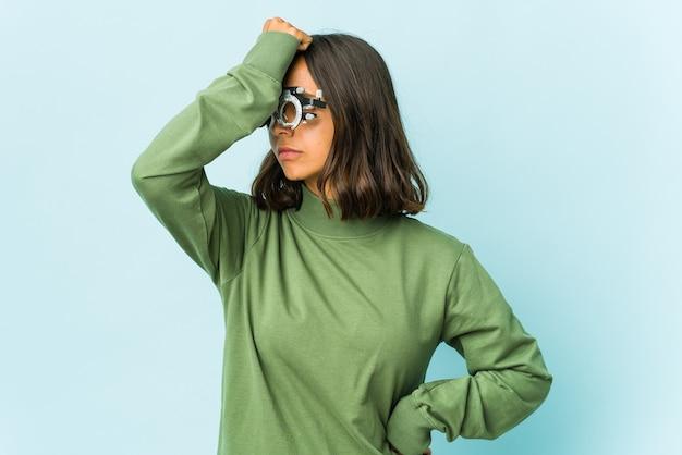 Молодая латинская женщина-окулист над изолированной стеной, что-то забывая, хлопает ладонью по лбу и закрывает глаза.