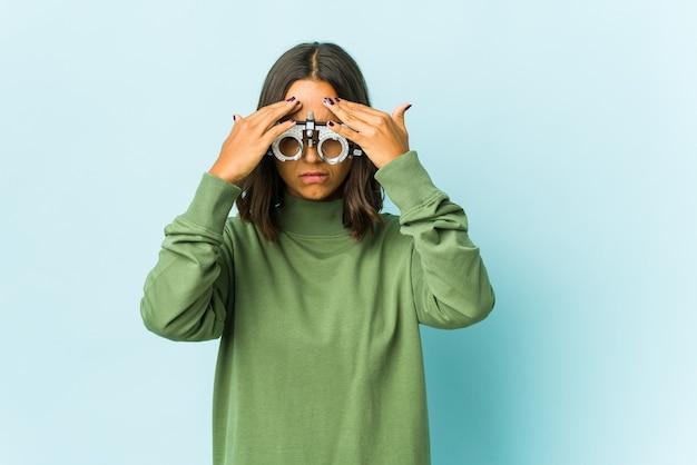 Молодая женщина-окулист из латинской америки над изолированной стеной, имеющей головную боль, касаясь передней части лица.