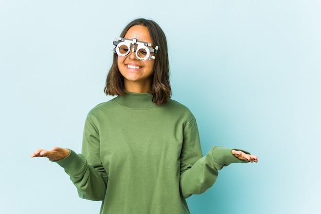 Латинская женщина молодой окулист над изолированной стеной держит что-то ладонями, предлагая камеру.