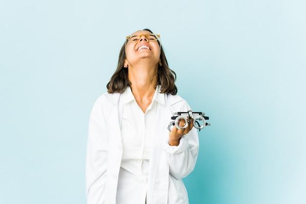 Молодой окулист латинской женщины над изолированной стеной расслабился и счастливый смех, вытянув шею, показывая зубы.