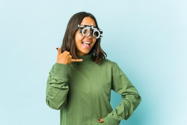 指で携帯電話の呼び出しジェスチャーを示す孤立した壁の上の若い眼科医ラテン女性。