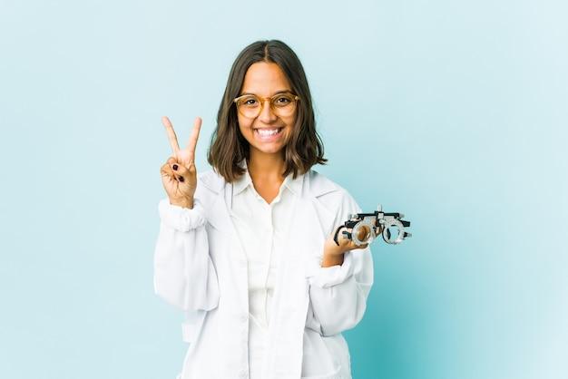Молодая латинская женщина-окулист над изолированной стеной показывает номер два пальцами.