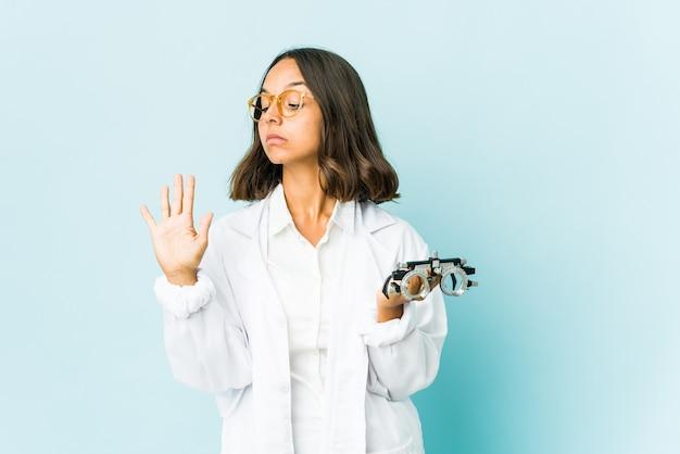 指で5番を示す陽気な笑顔の孤立した壁の上の若い眼科医ラテン女性。