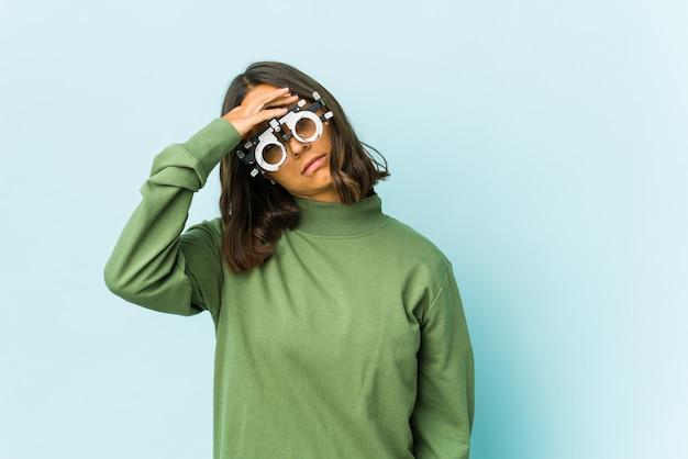 Молодая латинская женщина-окулист над изолированной стеной, касающейся висков и имеющей головную боль.