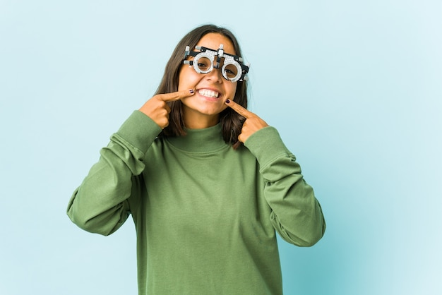Young oculist latin woman smiles, pointing fingers at mouth.