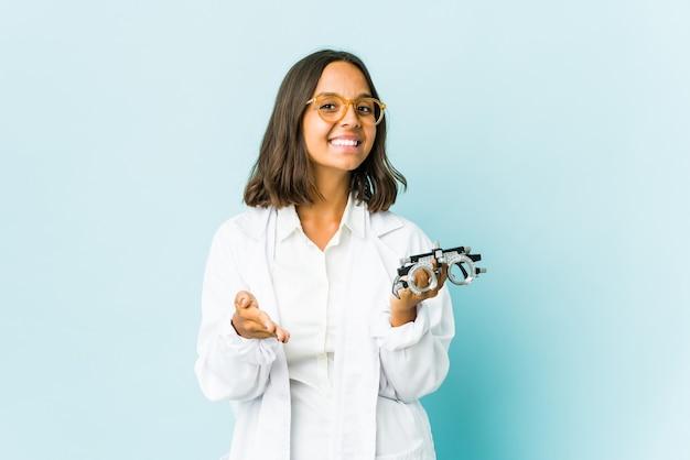 Латинская женщина молодого окулиста протягивая руку в приветствии жест.