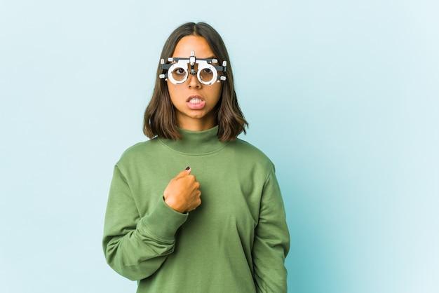 Латинская женщина молодой окулист удивлена указывая пальцем, широко улыбаясь.