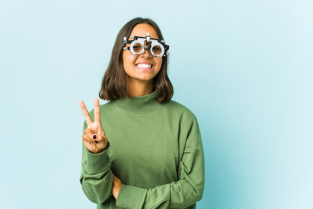 Young oculist woman over isolated wall showing number two with fingers