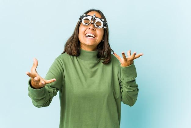 Молодая женщина-окулист чувствует себя уверенно, обнимая перед изолированной стеной