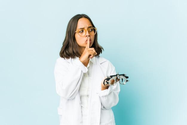 Молодая женщина-окулист над изолированной стеной хранит секрет или просит молчания