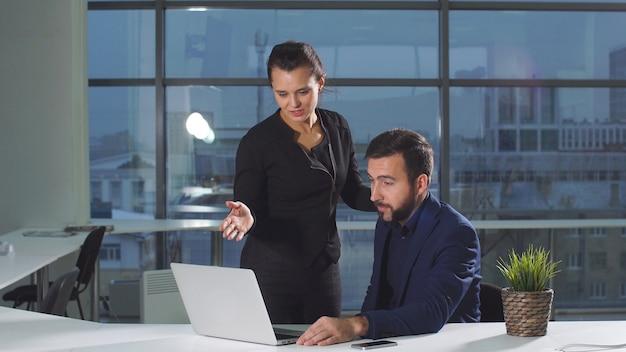若いオフィスの同僚がオンラインプロジェクトについて話し合いながらコンピューターで作業している