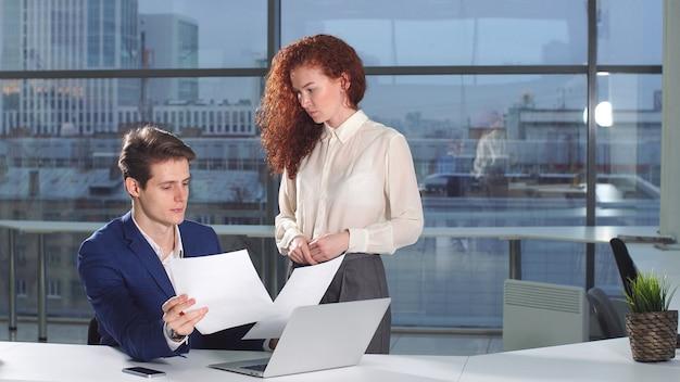 若いオフィスの同僚は、新しい戦略を議論する紙の文書で作業します
