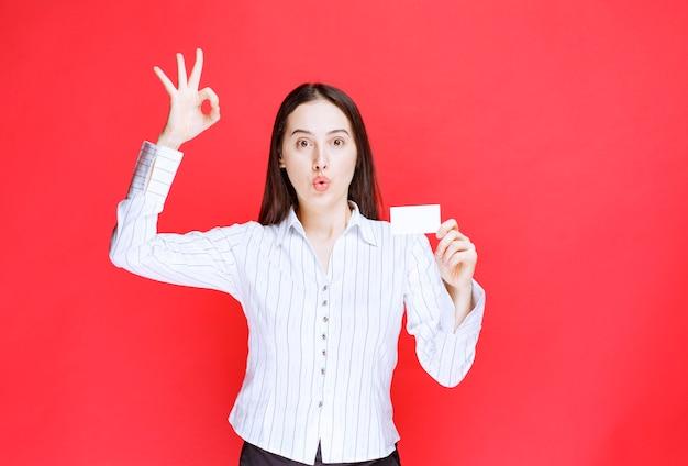 Молодой служащий офиса показывая визитную карточку и давая одобренный знак.