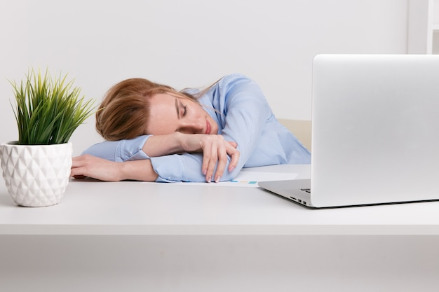 Young office girl sitting at her workplace feeling bad. woman has a headache.