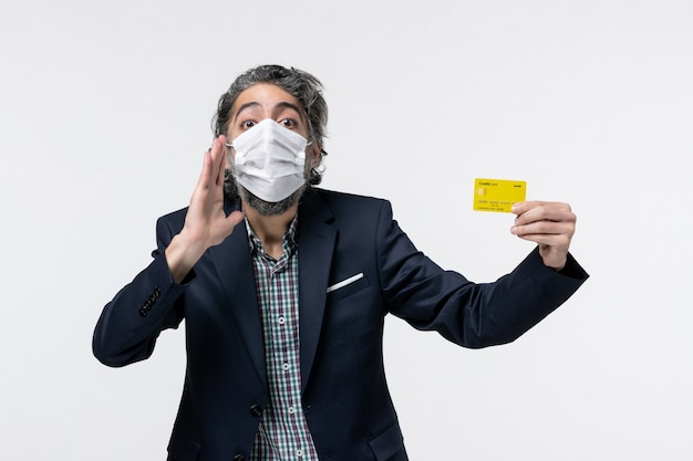 マスクを着用し、白い背景で何かを発表する彼の銀行カードを示すスーツを着た若いオフィスの男