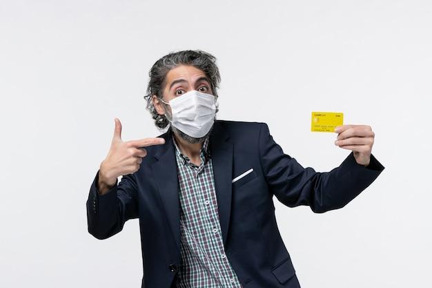 マスクを着用し、白い背景の左側に何かを指している彼の銀行カードを示すスーツを着た若いオフィスの男