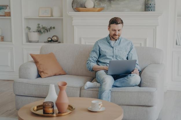 집에서 일하는 젊은 사무실 남성 노동자, 다리를 꼬고 노트북을 무릎에 얹고 거실 소파에 앉아 진행 중인 프로젝트 상태에 대해 동료들과 대화