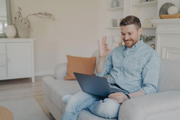 自宅から離れた場所で働く若いオフィスの男性労働者は、足を組んだモダンなリビングルームの快適なソファに座っている間、オンライン会議で上司に大丈夫なジェスチャーを示しています