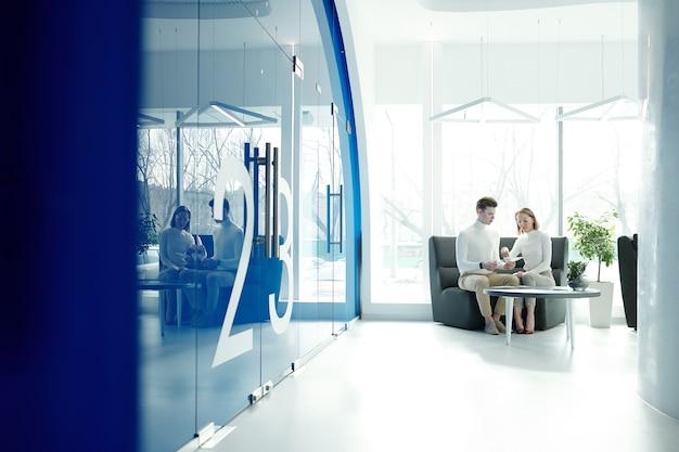 Молодой офис-менеджер демонстрирует клиентские характеристики и возможности новых футуристических прозрачных мобильных гаджетов.