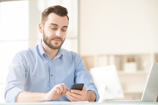 Young office manager using his smartphone for message communication while sitting in office