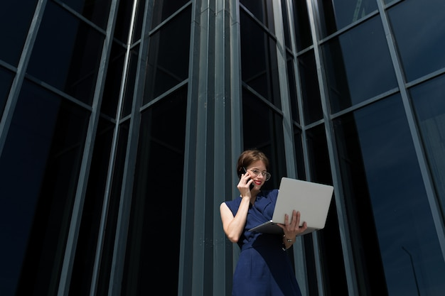 A young office serious woman stands near office and solve problems talking on the phone and with laptop