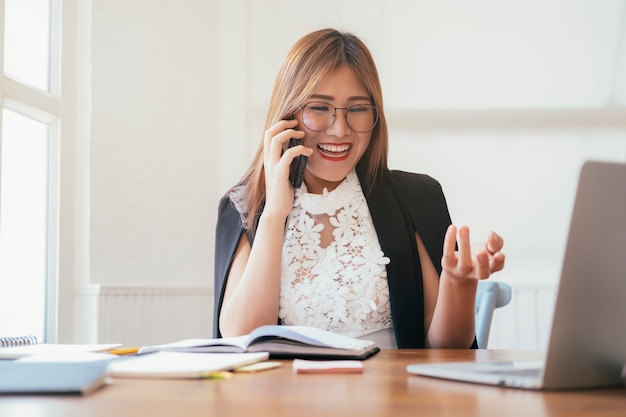 Young office woman talking on mobile phone.
