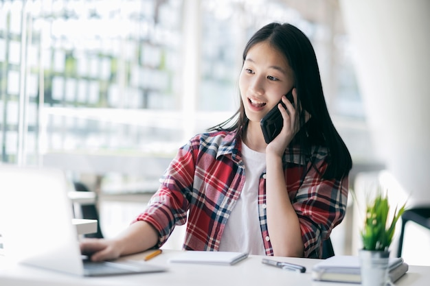 클라이언트와 휴대 전화에 얘기하는 젊은 사무실 여자.