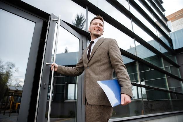 Молодой офисный работник входит в здание с папкой в руке