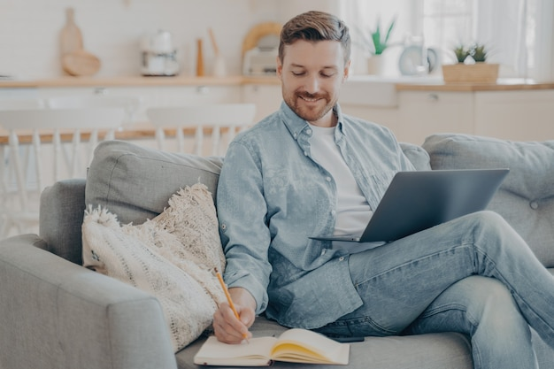 Young office worker working remotely from home, researching in internet using notebook, writing information down into red note book with pencil while sitting on cozy couch