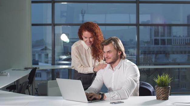現代のオフィスでラップトップを使用してオンラインプロジェクトを議論する若いサラリーマン