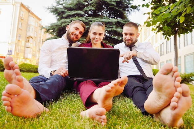Young office workers with bare feet sit on green lawn with a laptop and talk.