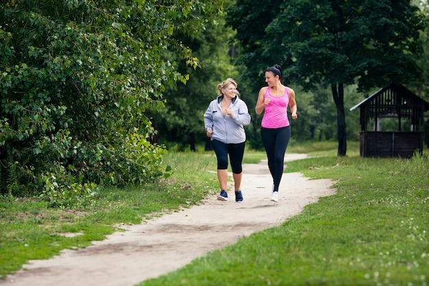 Young and old woman run nearby in summer park outdoors