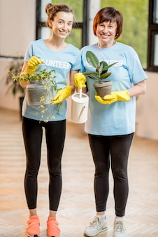 Young and older volunteers dressed in blue t-shirts taking care of green plants indoors
