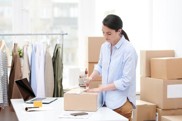 Молодой менеджер интернет-магазина с дозатором клейкой ленты, упаковывающий картонную коробку с заказом клиента в офисе