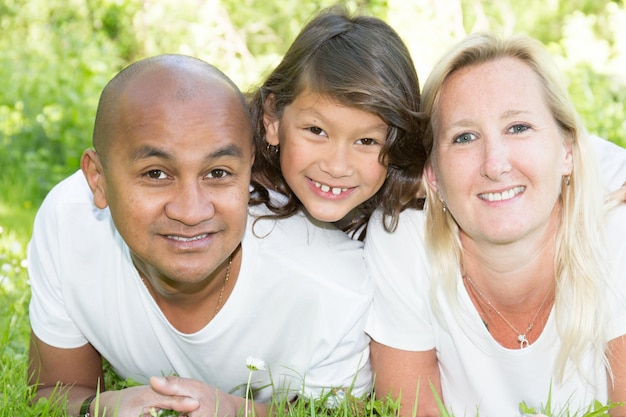 Young onterracial family with little child daughter lyong on green grass garden