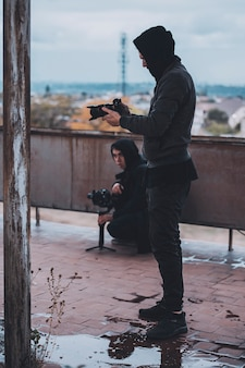 Young operator in hood shoots on camera with stab on the roof of abandoned house. work of professional.