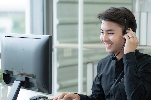 젊은 운영자는 고객을 돕기 위해 노력하고 있습니다.