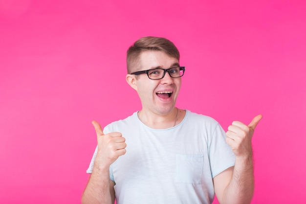 Young optimistic man on pink showing thumbs up with positive emotions of content and happiness.