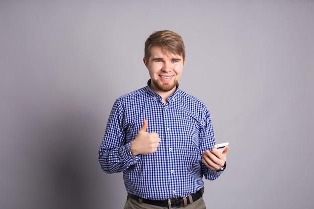 Молодой оптимистичный человек с мобильным телефоном на серой стене показывает палец вверх с положительными эмоциями