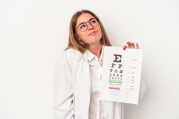 目標と目的を達成することを夢見て白い背景で隔離の若い検眼医ロシアの女性