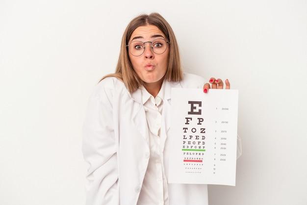 白い背景で隔離の若い検眼医ロシアの女性は肩をすくめ、目を開けて混乱します。