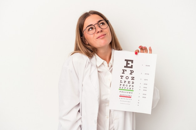 Young optometrist russian woman isolated on white background dreaming of achieving goals and purposes