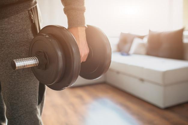Young ordinary man doing sports at home. holding dumbbells.
