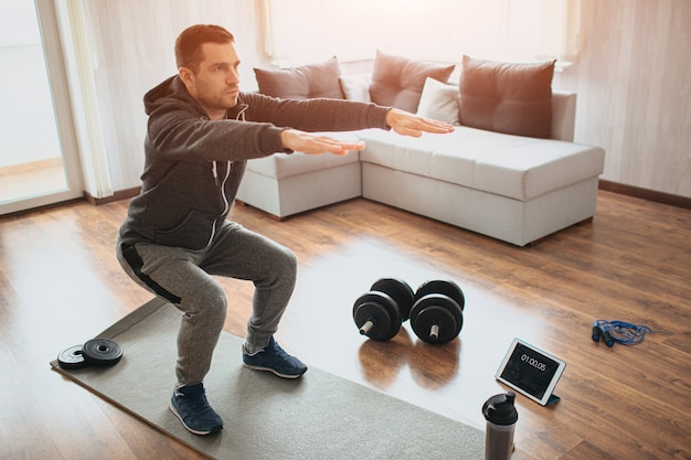 Young ordinary man doing sports at home. real picture of egular guy doing squats with stretch hands forward. beginner or amateur has workout in apartment. sport equipment on floor.