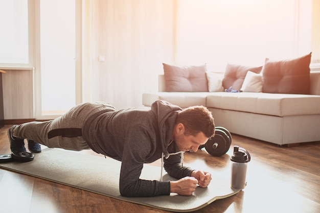 若い普通の人は家でスポーツに行きます。トレーニング中の新入生と初心者の男のフルサイズのpictrueはマットの板の位置に立っています