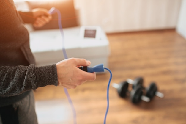 Young ordinary man go in for sport at home. cut view and close up of workout beginner holding jump rope with both hands