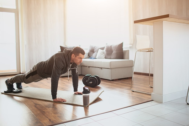 Young ordinary man go in for sport at home. full size picture of regular ordinary guy stand in plank position