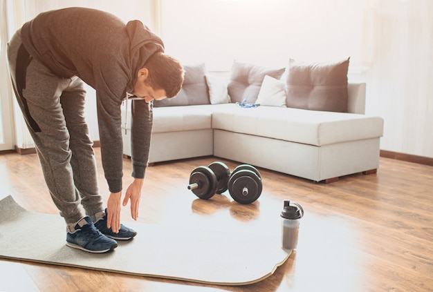 Young ordinary man go in for sport at home. stand on mat and stretch down to toes. ordinary guy warming out body before exercise. working out alone in middle of room. sport ewuipment on floor.
